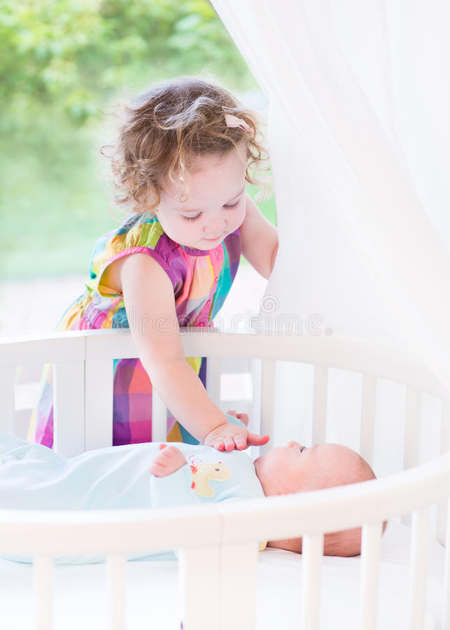 Cute toddler girl playing with newborn baby brother. Cute toddler girl playing with her newborn baby brother laying in white round crib royalty free stock image