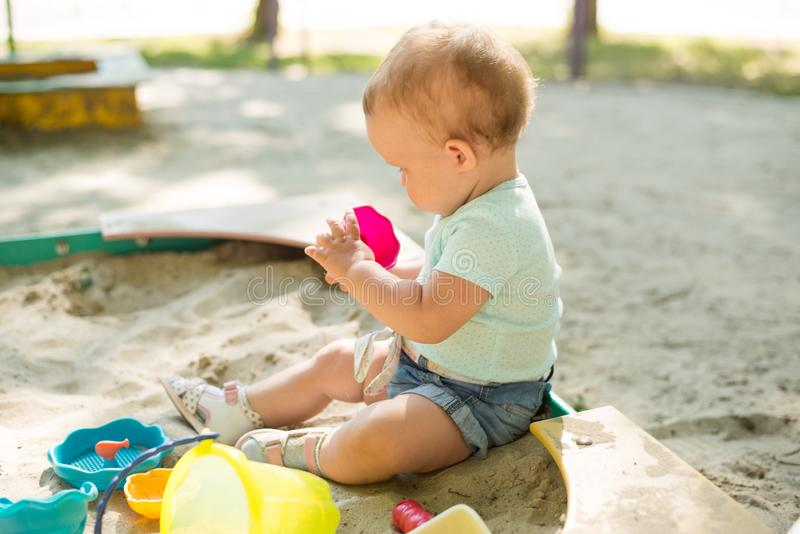 Cute toddler girl playing in sand on outdoor playground. Beautiful baby having fun on sunny warm summer day. Child with colorful stock photo