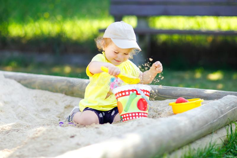 Cute toddler girl playing in sand on outdoor playground. Beautiful baby having fun on sunny warm summer sunny day. Happy stock photos