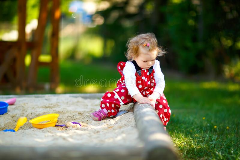 Cute toddler girl playing in sand on outdoor playground. Beautiful baby in red gum trousers having fun on sunny warm. Summer day. Child with colorful sand toys royalty free stock images