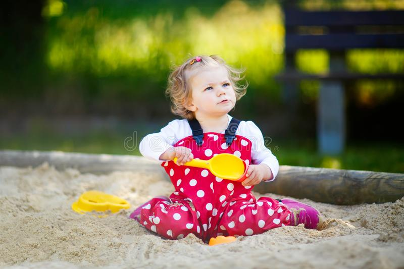 Cute toddler girl playing in sand on outdoor playground. Beautiful baby in red gum trousers having fun on sunny warm. Summer day. Child with colorful sand toys stock image