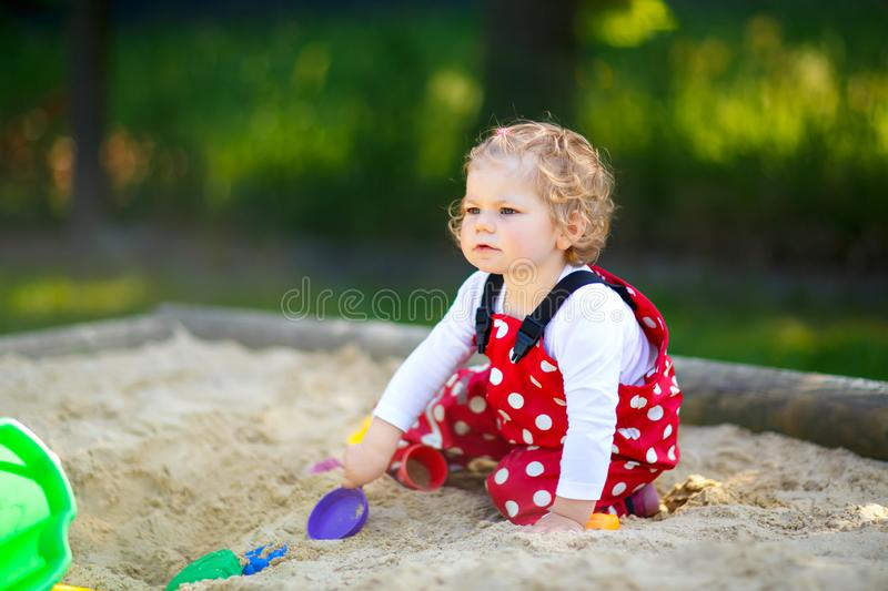 Cute toddler girl playing in sand on outdoor playground. Beautiful baby in red gum trousers having fun on sunny warm. Summer day. Child with colorful sand toys stock photos