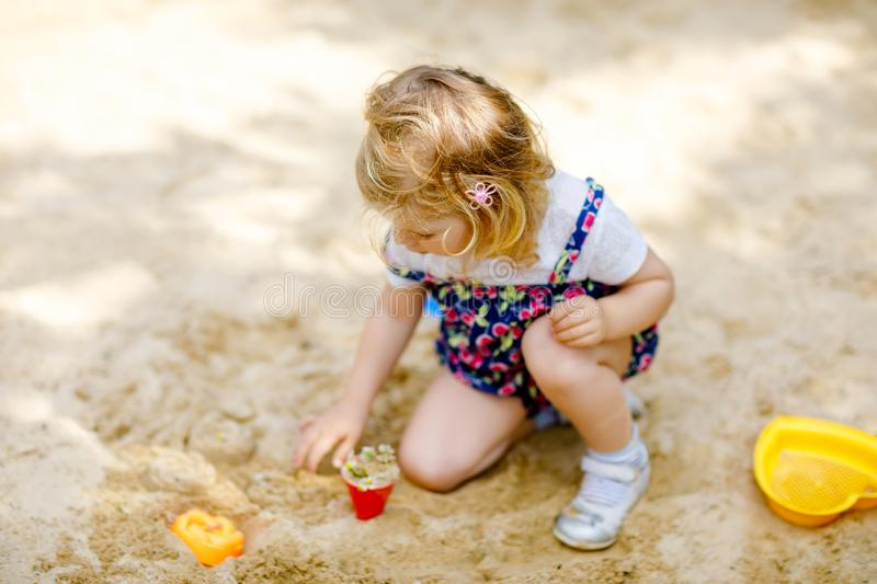 Cute toddler girl playing in sand on outdoor playground. Beautiful baby in red trousers having fun on sunny warm summer. Day. Child with colorful sand toys royalty free stock photo