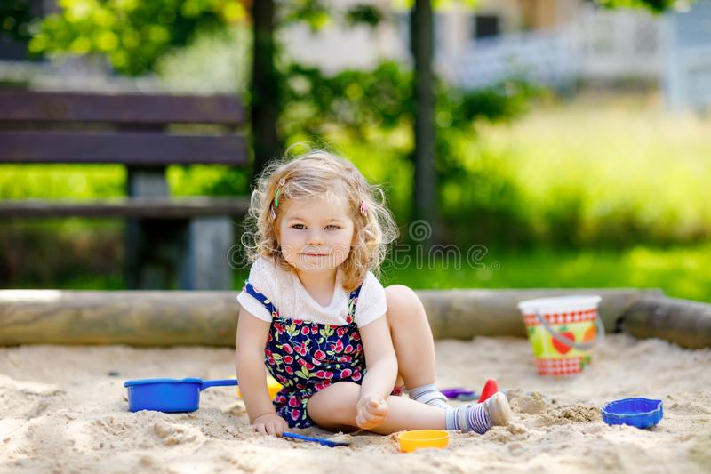 Cute toddler girl playing in sand on outdoor playground. Beautiful baby in red trousers having fun on sunny warm summer. Day. Child with colorful sand toys stock photos