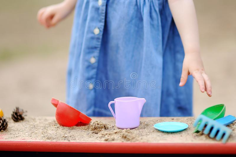 Cute toddler girl playing in a sandbox with moulds and pinecones royalty free stock photography