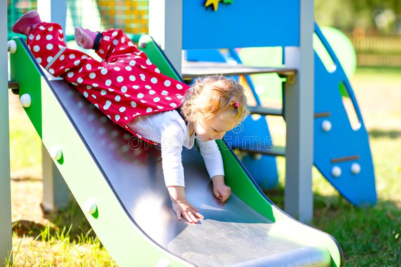 Cute toddler girl playing on slide on outdoor playground. Beautiful baby in red gum trousers having fun on sunny warm stock photo