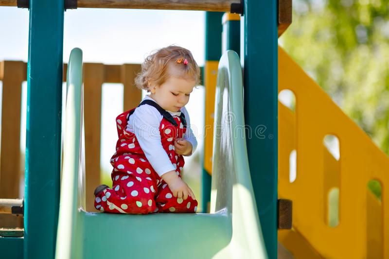 Cute toddler girl playing on slide on outdoor playground. Beautiful baby in red gum trousers having fun on sunny warm. Summer day. Child sliding down royalty free stock photos