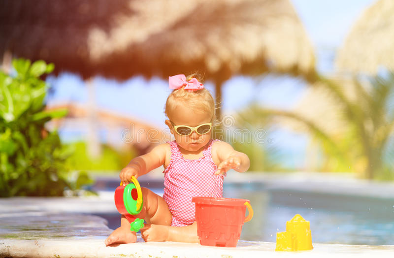 Cute toddler girl playing in swimming pool at beach. Cute toddler girl playing in swimming pool at tropical beach royalty free stock images