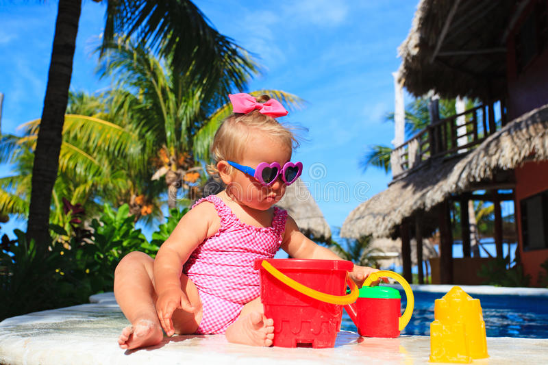 Cute toddler girl playing in swimming pool at the. Cute toddler girl playing in swimming pool at tropical beach stock images