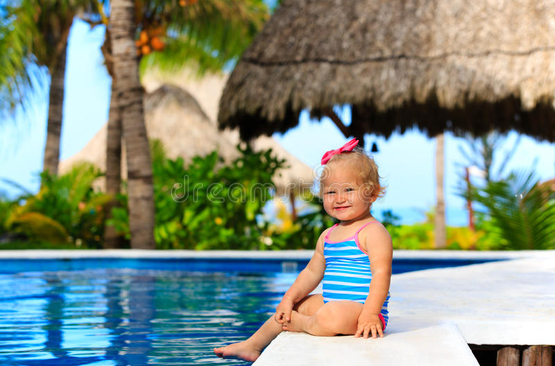 Cute toddler girl playing in swimming pool at. Tropical beach royalty free stock images