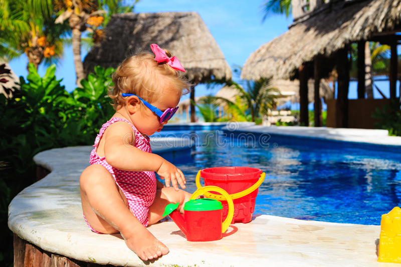 Cute toddler girl playing in swimming pool at the. Cute toddler girl playing in swimming pool at tropical beach stock photography