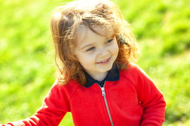 Cute toddler looking away on green grass royalty free stock photo