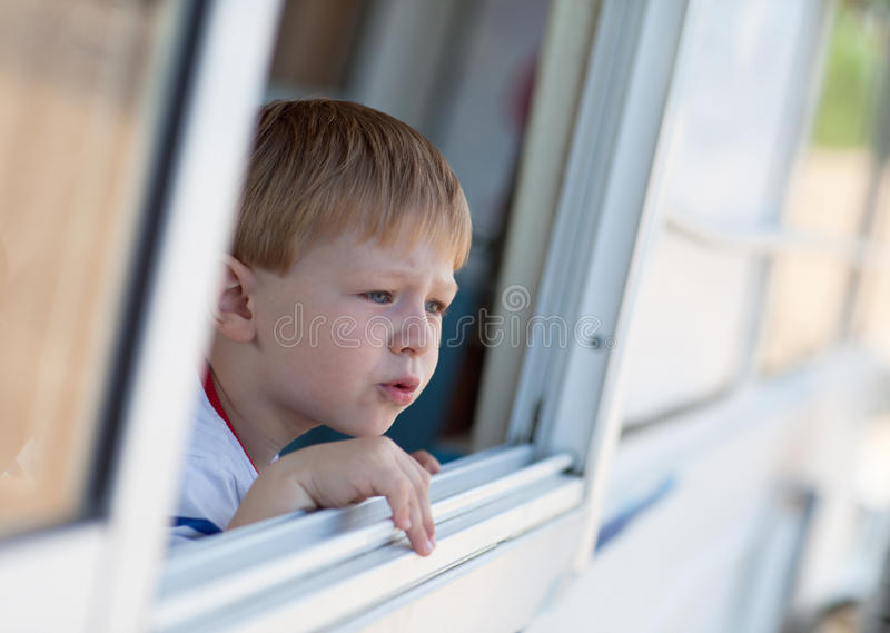 Cute toddler in an open window stock photo