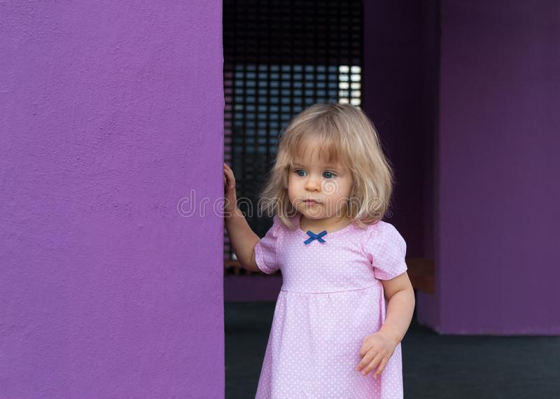Cute toddler in pink summer dress in peas 1 year old outdoors. Looking away. Childhood. Portrait of serious and beautiful blonde royalty free stock photo