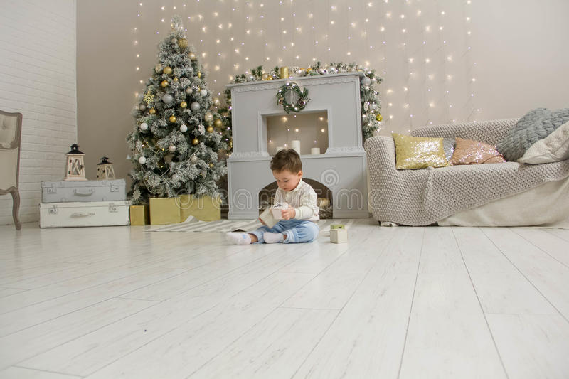 Cute toddler playing with his Christmas present in the decorated room. wooden toy. Family Xmas morning in decorated. Living room with kids gifts, fireplace royalty free stock image