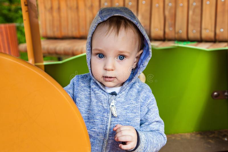 Cute toddler playing on the playground in spring sunny. close-up portrait of a boy in the toy house. royalty free stock photography