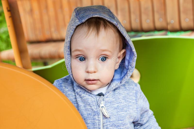 Cute toddler playing on the playground in spring sunny. close-up portrait of a boy in the toy house. stock image