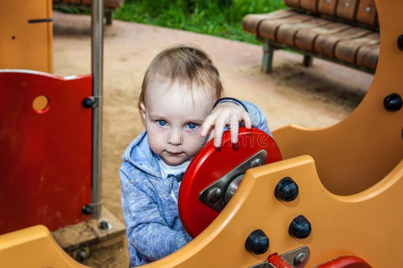 Cute toddler playing on the playground in spring sunny. close-up portrait of a boy in the toy house. stock images