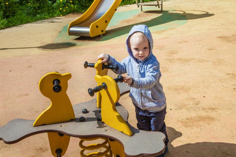 Cute toddler playing on the playground in spring sunny day. funny boy sitting on a swing . stock images