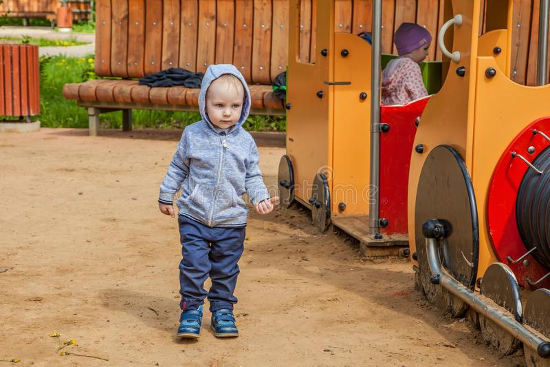 Cute toddler playing on the playground in spring sunny day. funny boy stands near the children`s train. stock image