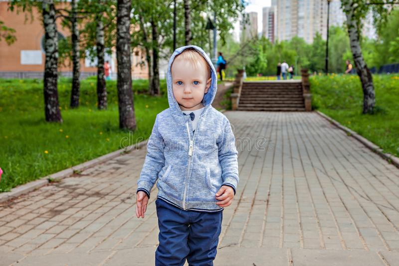 Cute toddler playing on the playground in spring sunny day. smart cheerful boy on a walk. . stock images