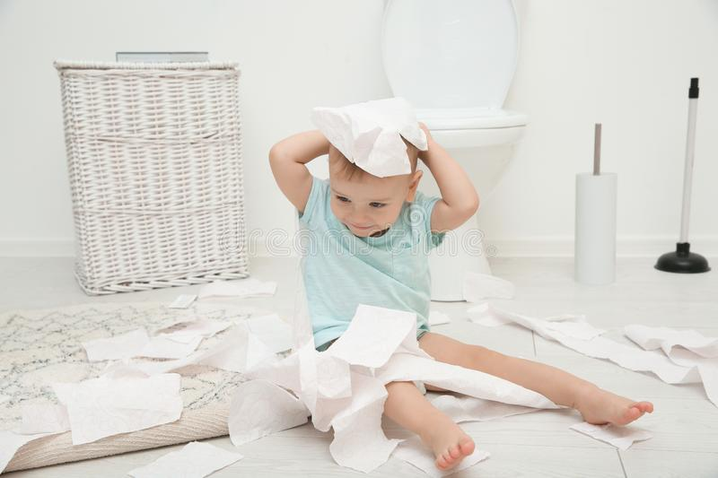 Cute toddler playing with toilet paper. In bathroom royalty free stock photo