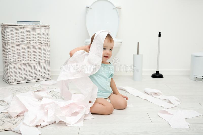 Cute toddler playing with toilet paper. In bathroom royalty free stock image