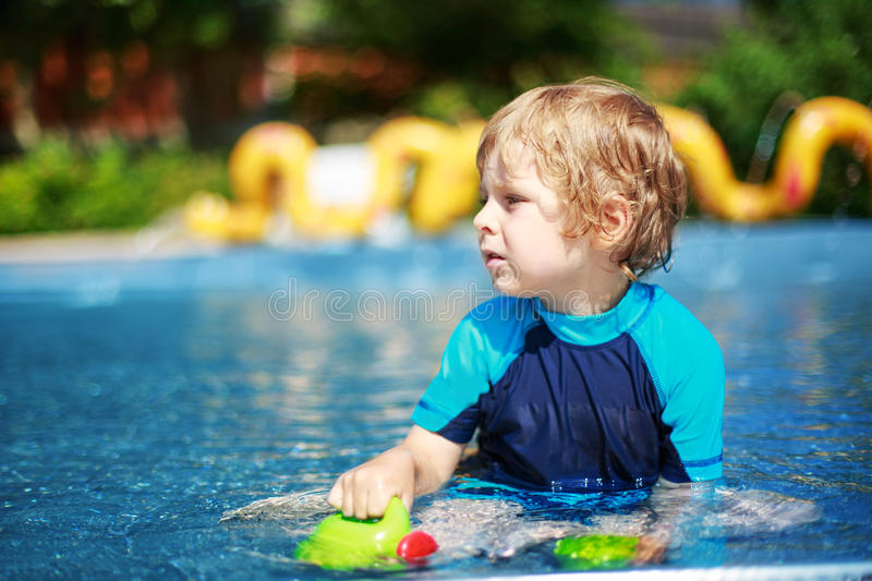 Cute toddler playing with water by the outdoor swimming pool. Cute boy of 3 years in protection swimming suit having fun with water in outdoor swimming pool stock photo