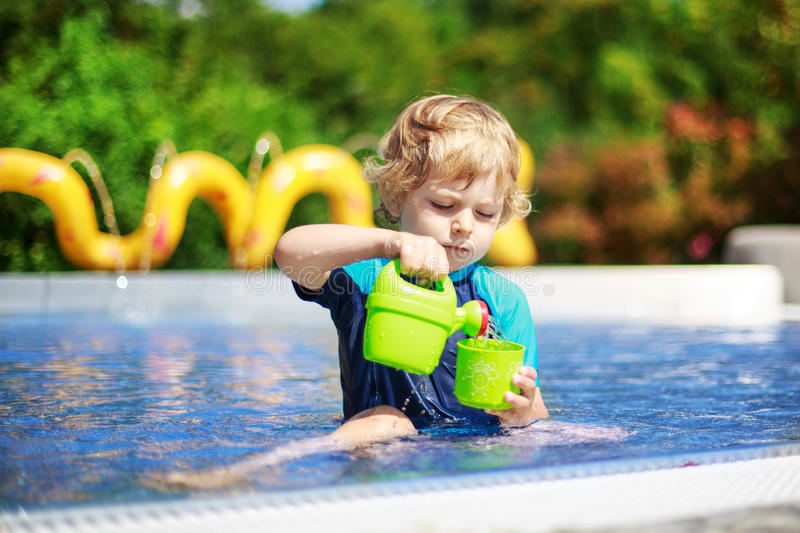 Cute toddler playing with water by the outdoor swimming pool. Cute boy of 3 years in protection swimming suit having fun with water in outdoor swimming pool royalty free stock images