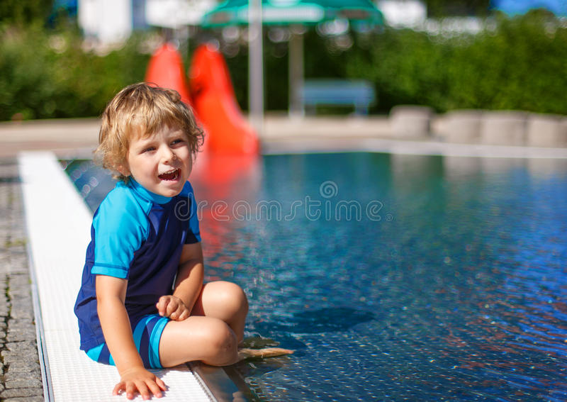 Cute toddler playing with water by the outdoor swimming pool. Cheerful toddler playing with water by the outdoor swimming pool royalty free stock image