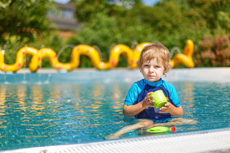 Cute toddler playing with water by the outdoor swimming pool. Cheerful toddler playing with water by the outdoor swimming pool stock photo
