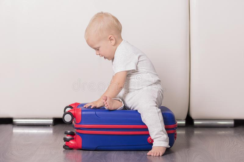 Cute toddler sitting on the suitcase. Funny baby boy going to vacation stock images