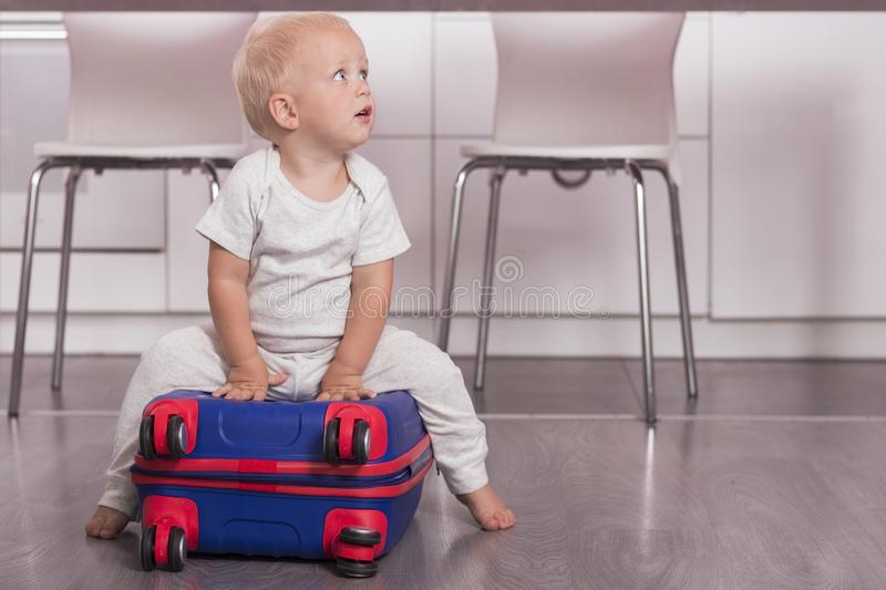Cute toddler sitting on the suitcase. Funny baby boy going to vacation stock image