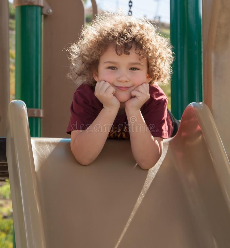 Download Curly haired boy on slide stock photo. Image of happy - 30366324