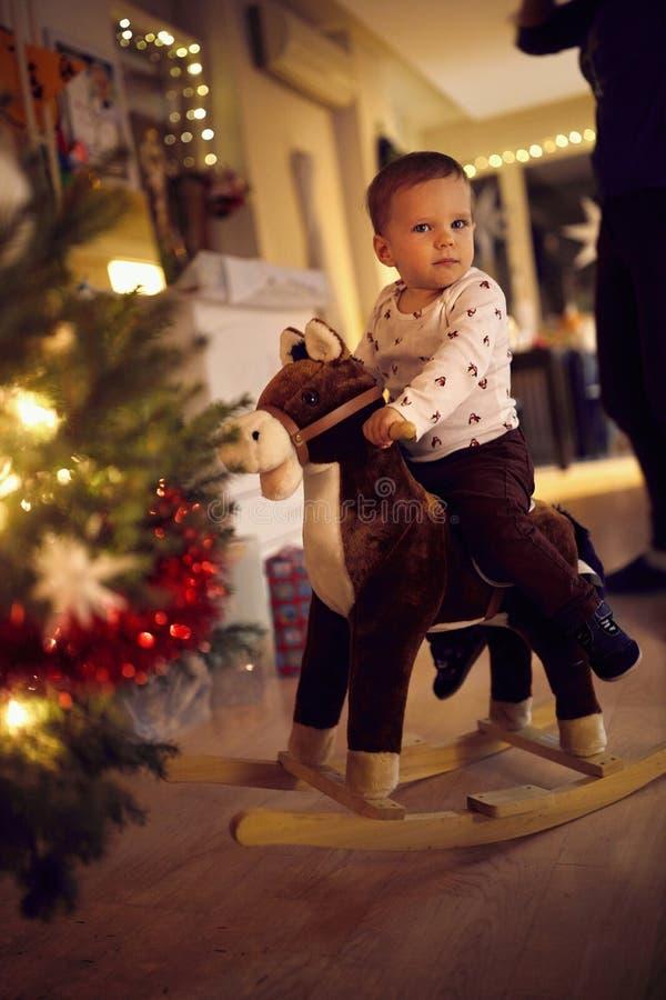 Cute toddler speelt op zaai paard bij Christams boom royalty-vrije stock foto's