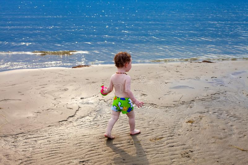 Cute toddler walks the beach royalty free stock images
