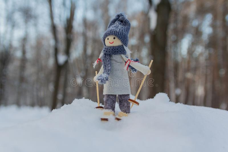 Cute toy girl skiing in the snowy forest stock image