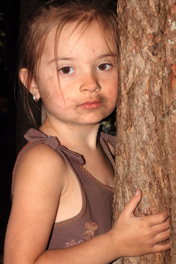 Cute Treehugger. A closeup of a cute dirty little 4 year old girl with messy brown hair, wearing a brown swimsuit hugging a tree trunk. Shallow depth of field royalty free stock photo