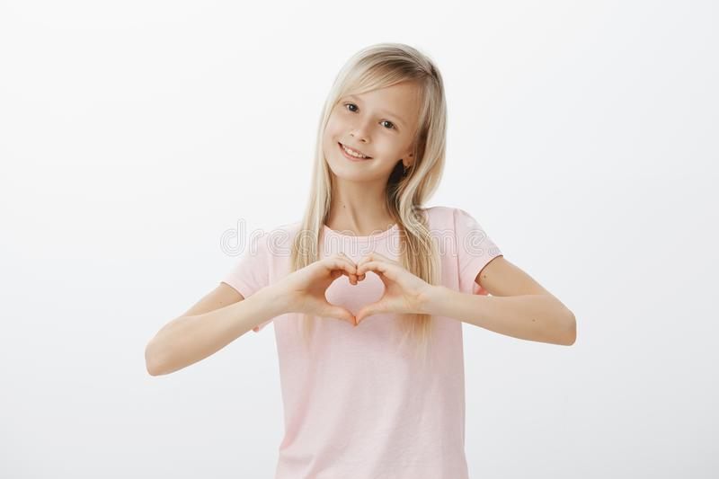 Cute trendy young girl loving her cat. Indoor shot of adorable little woman with pleased expression, showing heart. Gesture and smiling broadly, confessing in royalty free stock images