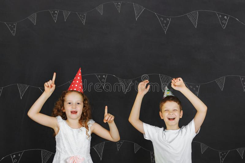 Cute twins kids with carnival hat at celebration birthday party. Holiday concept stock photography
