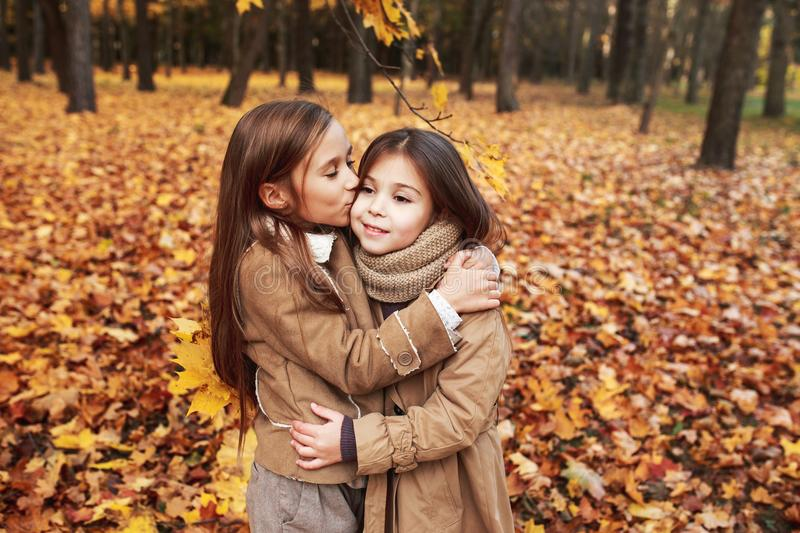 Cute two little sisters hugging in autumn park outdoor. Cute two little sisters hugging in autumn park royalty free stock images