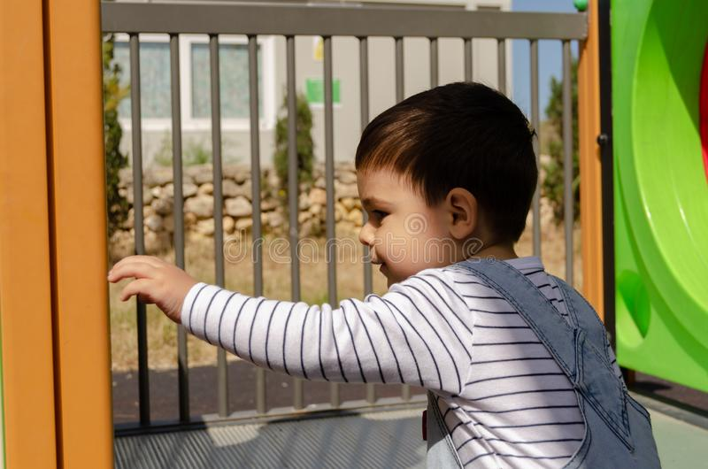 Cute two years old boy playig in the children playground outdoors on the playhouse stock images