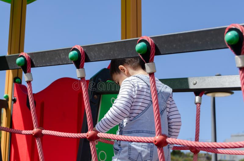 Cute two years old boy playig in the children playground outdoors on the playhouse stock photo