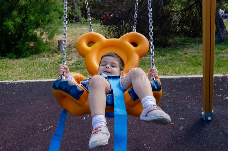 Cute two years old boy playig in the children playground outdoors on the teddy bear swing stock photography