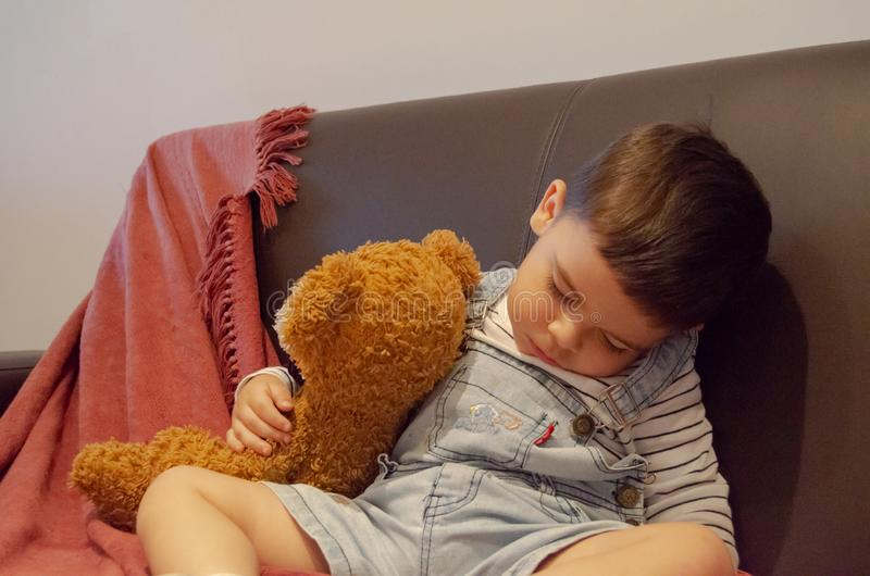 Cute two years old sleeping while sitting on the sofa and hugging teddy bear stock photo