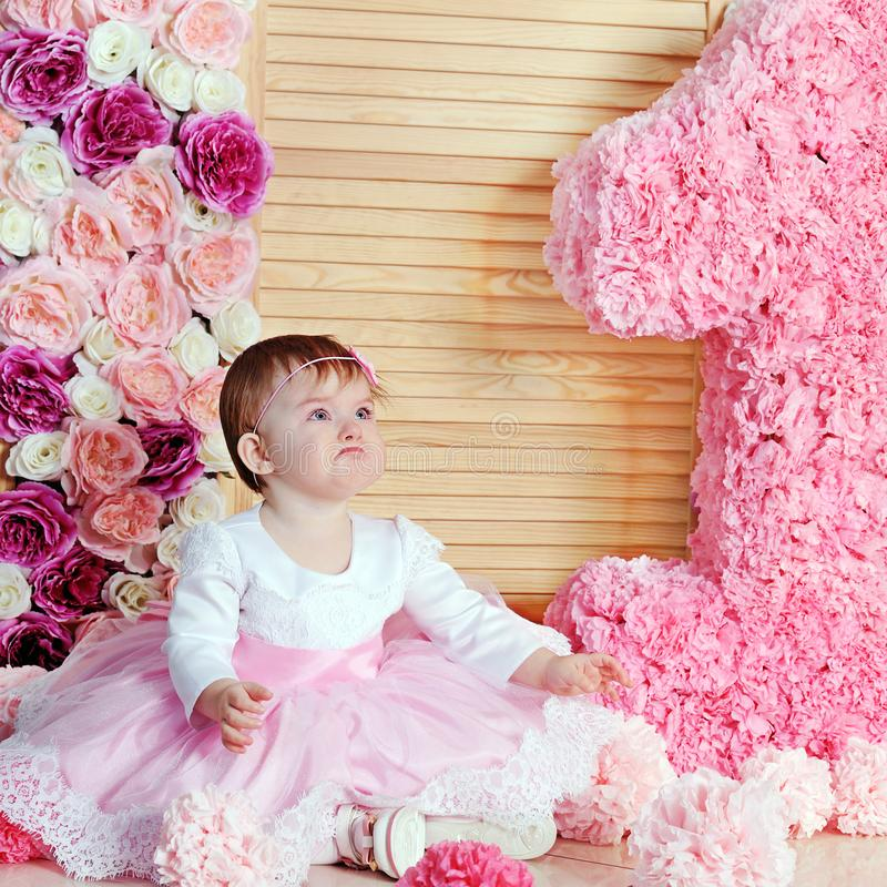 Cute upset baby girl in pink dress royalty free stock image