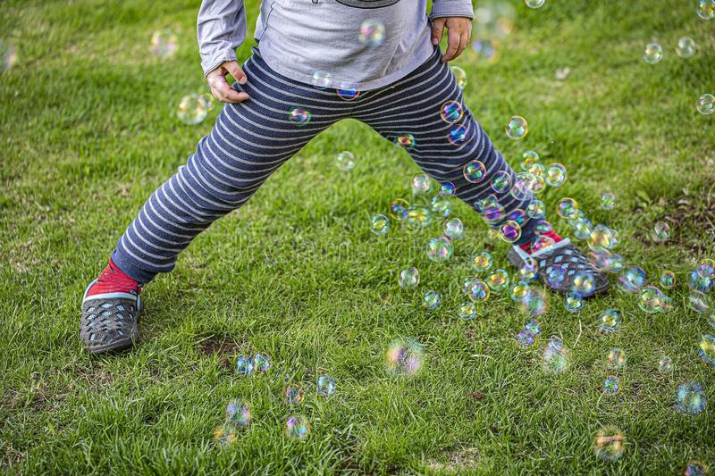Cute view of child figure plying with colorful bubbles on green lawn. Beautiful backgrounds.  royalty free stock image
