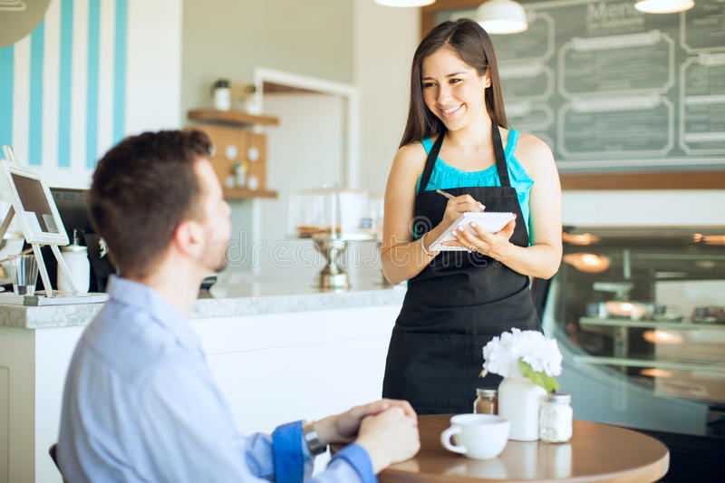 Cute waitress taking an order. Portrait of a beautiful friendly waitress taking an order from a customer and writing it down on a notepad royalty free stock image