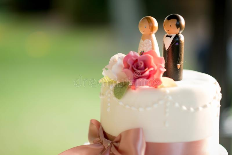 Cute wedding cake figures over an elegant white wedding cake with roses royalty free stock images