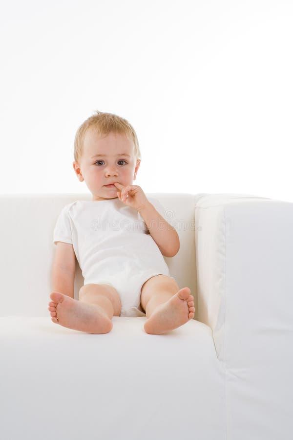Cute white boy on sofa stock photography